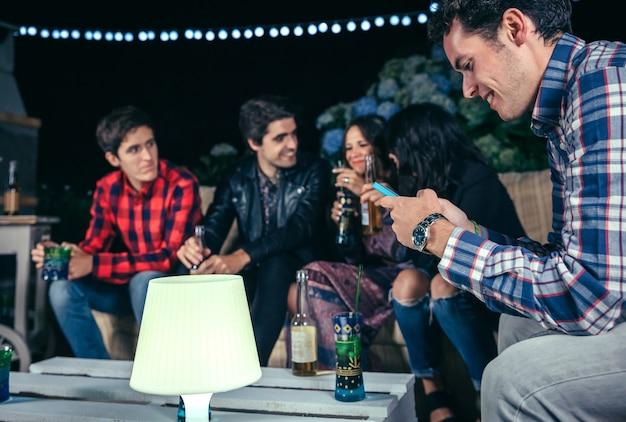 Portrait d'un homme heureux regardant son smartphone dans une fête en plein air avec des amis. concept d'amitié et de célébrations.