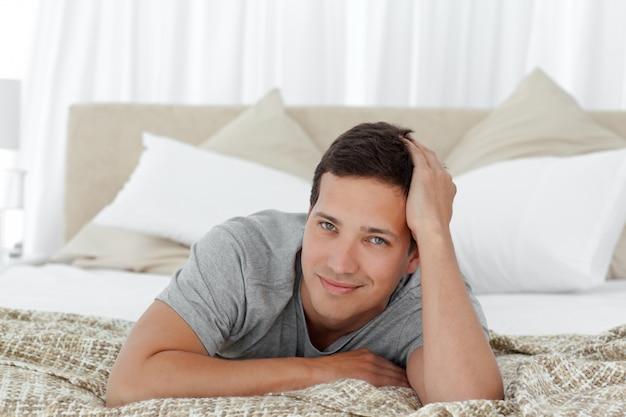 Portrait d'un homme heureux reposant sur son lit
