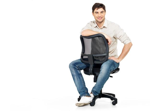 Portrait d'homme heureux souriant est assis sur la chaise de bureau isolée sur blanc.