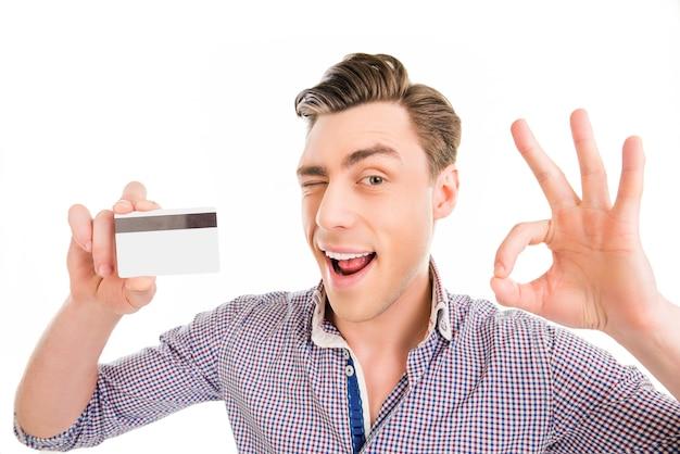 Portrait d'un homme heureux tenant une carte bancaire et faisant des gestes