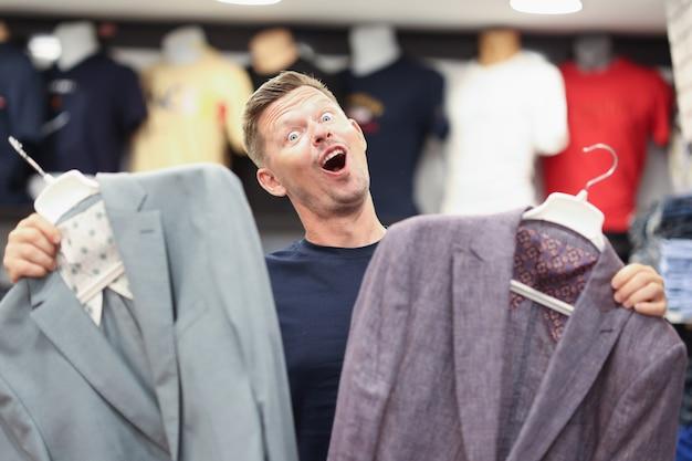 Portrait d'un homme heureux tenant deux vestes en magasin en choisissant un concept de costume pour hommes