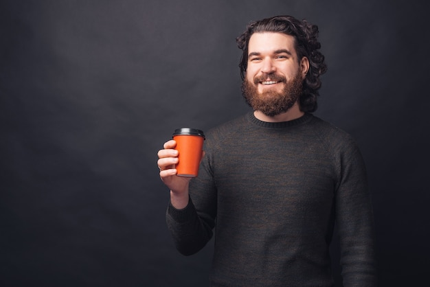 Portrait d'un homme heureux tenant une tasse de café rouge pour aller sur le mur noir