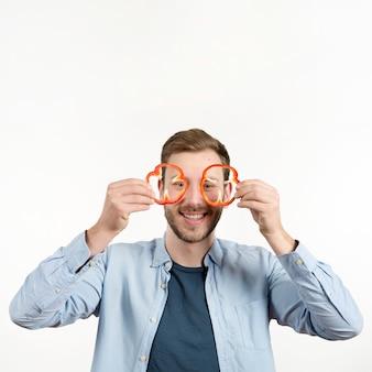 Portrait d'un homme heureux, tenant des tranches de poivrons devant ses yeux
