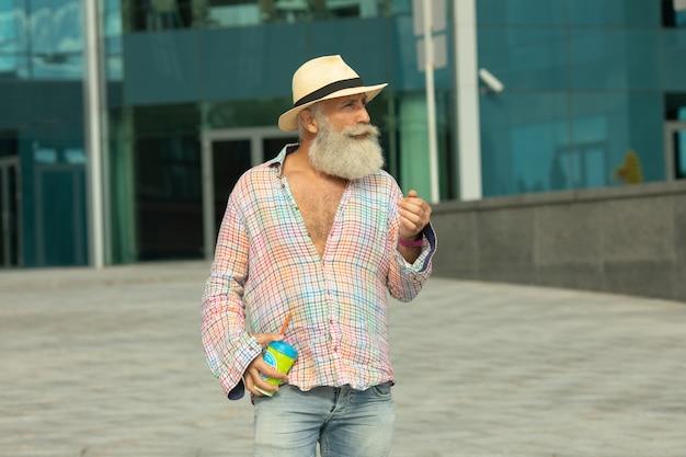 Portrait d'homme hipster barbu senior positif ayant une pause-café à l'extérieur en milieu urbain.
