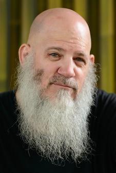 Portrait d'homme hipster chauve mature avec une longue barbe contre le mur de bambou à l'extérieur