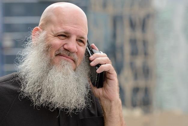 Portrait d'homme hipster chauve mature avec une longue barbe contre vue sur la ville en plein air