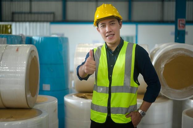 Portrait d'homme ingénieur mettant un casque de protection sur la tête dans l'entrepôt