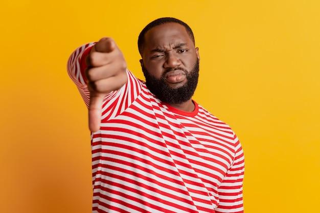 Portrait d'un homme insatisfait montrant le geste du pouce vers le bas sur fond jaune