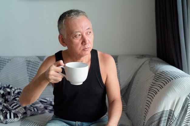 Portrait d'homme japonais mature, boire du café et penser dans le salon