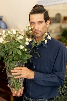 Portrait d'homme jardinier aux cheveux longs tenant des fleurs