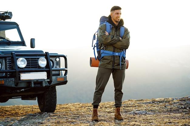 Portrait d'un homme jeune voyageur dans l'équipement de randonnée debout près de sa voiture tout-terrain