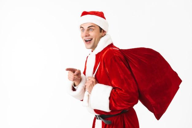 Portrait d'homme joyeux des années 30 en costume de père noël et chapeau rouge marchant avec sac-cadeau sur l'épaule