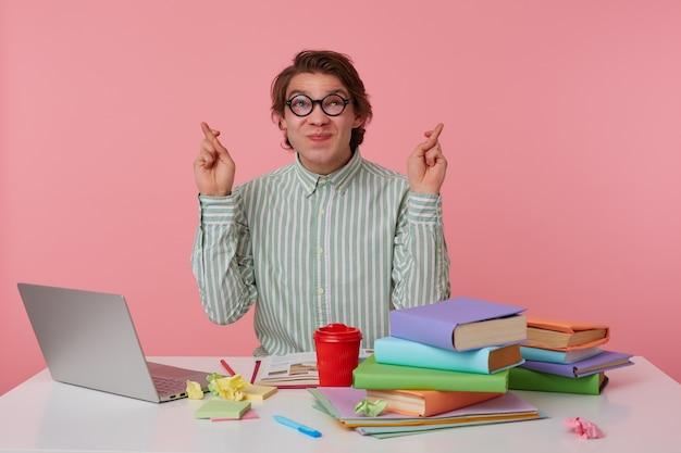 Portrait d'un homme à lunettes, assis à une table avec des livres, travaillant sur un ordinateur portable, lève les yeux avec les doigts croisés, espère bonne chance, isolé sur fond rose.