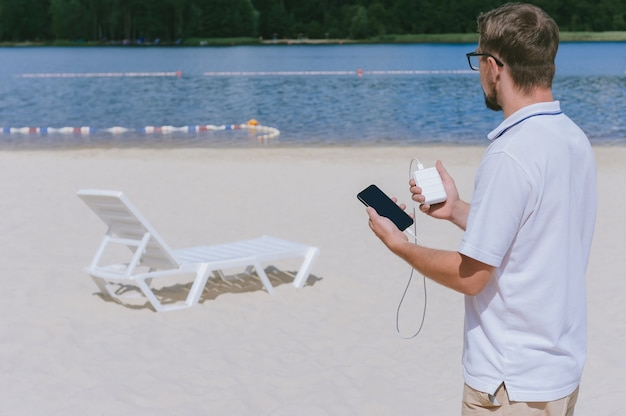Portrait d'un homme avec des lunettes chargeant un smartphone à partir d'une banque d'alimentation sur la plage. sur fond de sable, transat et eau.