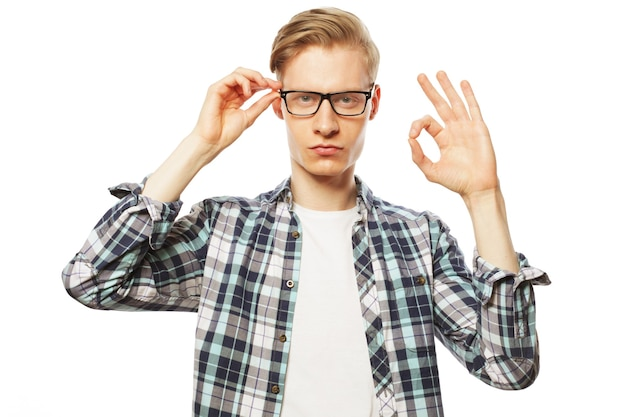 Portrait d'un homme à lunettes montrant le pouce vers le haut sur fond blanc