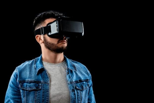Portrait d'un homme à lunettes de réalité virtuelle, vr, sur un fond sombre.
