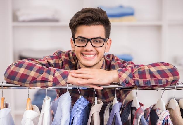 Portrait d'un homme à lunettes se penchant sur un rack avec des vêtements.