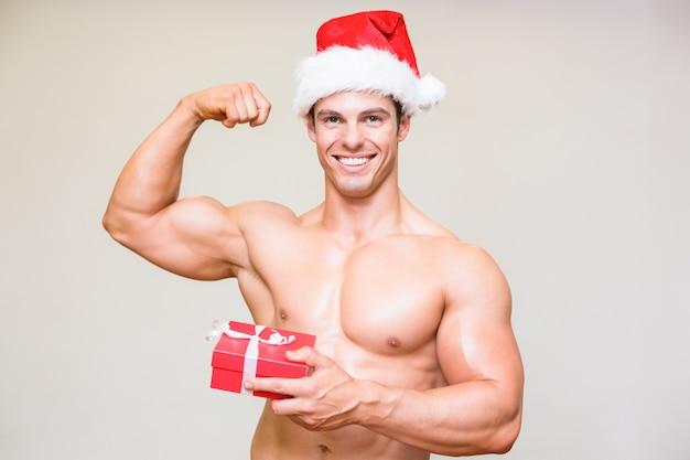 Portrait, de, homme macho torse nu, dans, santa, chapeau, tenue, cadeau