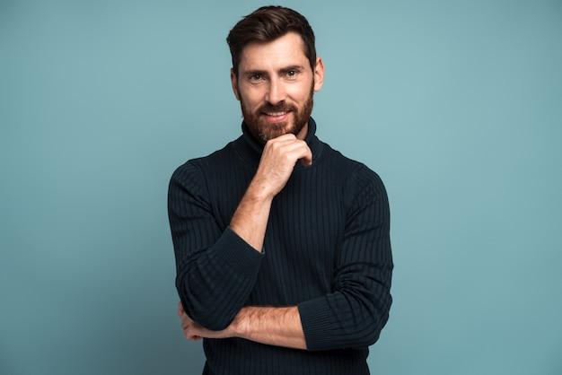 Portrait d'un homme mal rasé heureux debout avec la main près de son visage et souriant à la caméra. concept d'apparence masculine. studio intérieur tourné isolé sur bleu