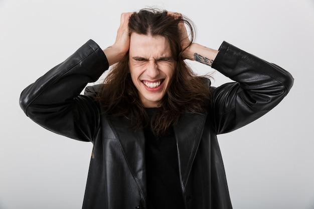 Portrait d'un homme malade brune aux cheveux longs portant une veste en mousse saisissant sa tête et ayant des maux de tête sur blanc