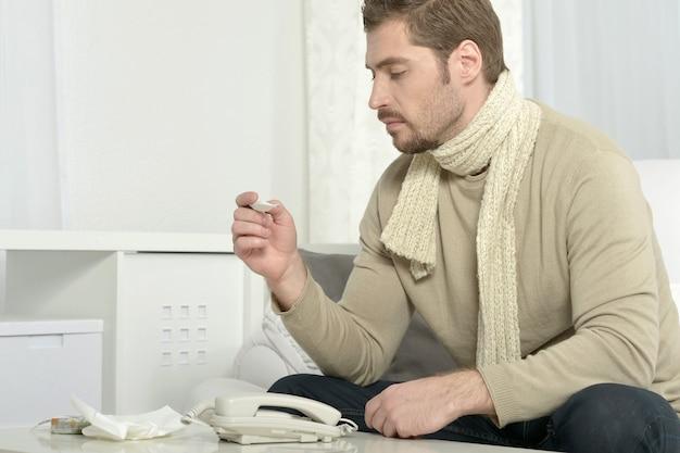 Portrait d'un homme malade avec thermomètre
