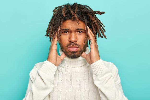Portrait d'un homme malheureux à la peau sombre avec des dreads, souffre d'une tête insupportable, garde les mains sur les tempes, porte un pull blanc avec col, isolé sur fond bleu, demande des analgésiques