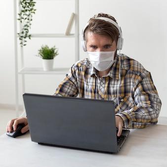 Portrait d'homme avec masque facial travaillant à domicile