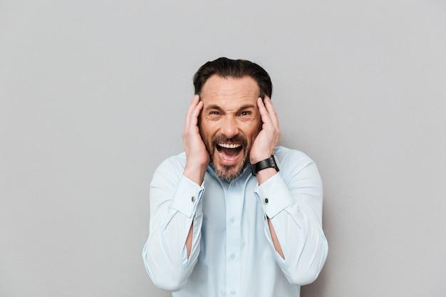 Portrait d'un homme mature en colère vêtu d'une chemise hurlant