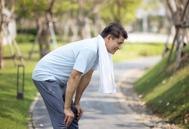 Portrait d'homme mature sain sportif en sweat à capuche et chaussures de course exerçant à l'extérieur, pratiquant des fentes latérales. homme barbu âgé en tenue de sport s'échauffant avant de courir le matin dans le parc