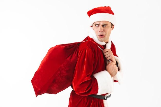 Portrait d'homme mécontent des années 30 en costume de père noël et chapeau rouge marchant avec sac-cadeau sur l'épaule