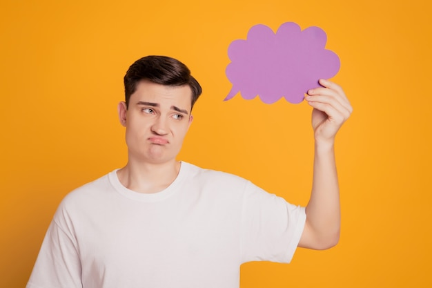 Portrait d'un homme mécontent contrarié tenant la main d'un nuage créatif avec un espace vide sur fond jaune