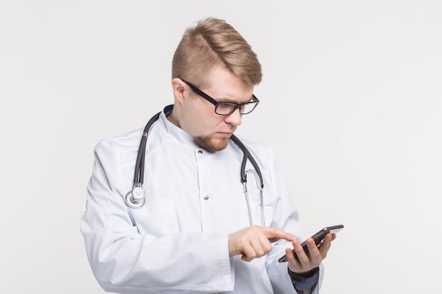Portrait d'homme médecin avec smartphone en mains sur blanc
