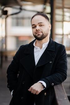 Portrait d'un homme à la mode bien habillé avec barbe posant à l'extérieur