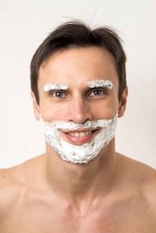 Portrait d'un homme avec de la mousse à raser sur le visage