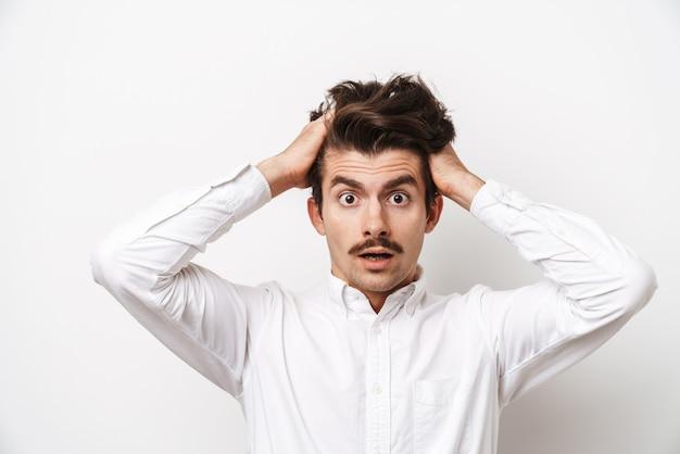 Portrait d'homme moustachu choqué portant chemise regardant à l'avant et saisissant sa tête isolé sur blanc