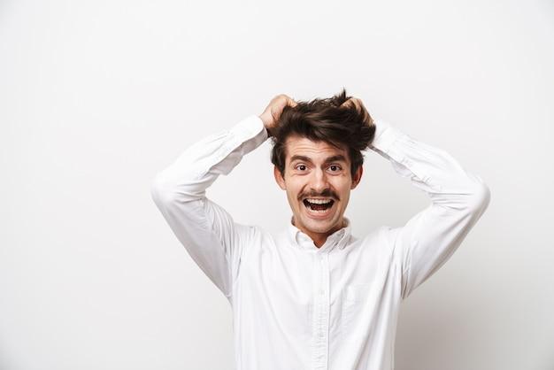 Portrait d'homme moustachu émotionnel portant chemise criant et saisissant sa tête isolé sur blanc
