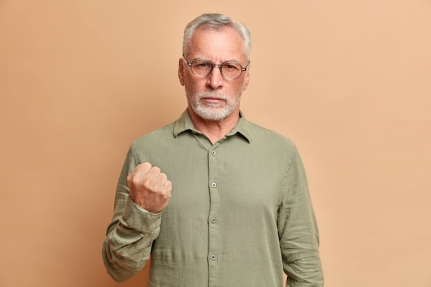Portrait d'homme mûr barbu irrité serre le poing et démontre la colère vous avertit habillé en chemise formelle pose contre le mur beige