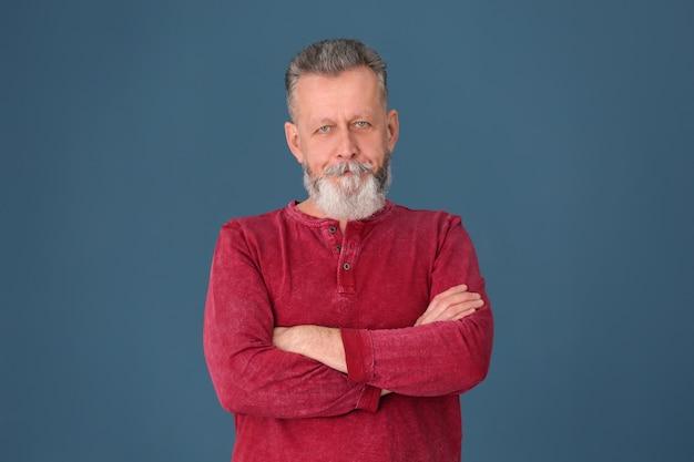 Portrait d'homme mûr confiant sur la surface de couleur
