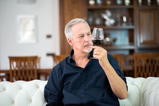 Portrait d'un homme mûr en dégustant un verre de vin rouge à la maison