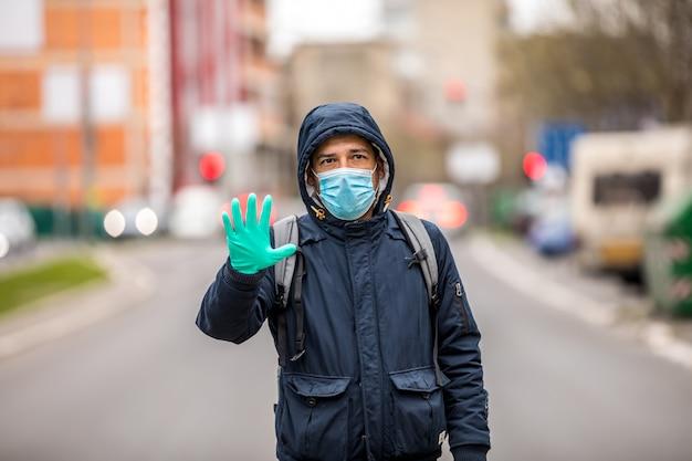 Portrait d'homme mûr, disant non à l'infection par le coronavirus avec le port d'un masque médical bleu chirurgical