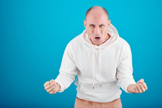 Portrait d'un homme mûr émotionnel en colère en sweat à capuche blanc criant et regardant la caméra