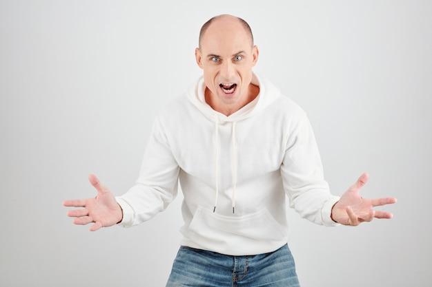 Portrait d'homme mûr furieux en colère en sweat à capuche blanc criant à la caméra
