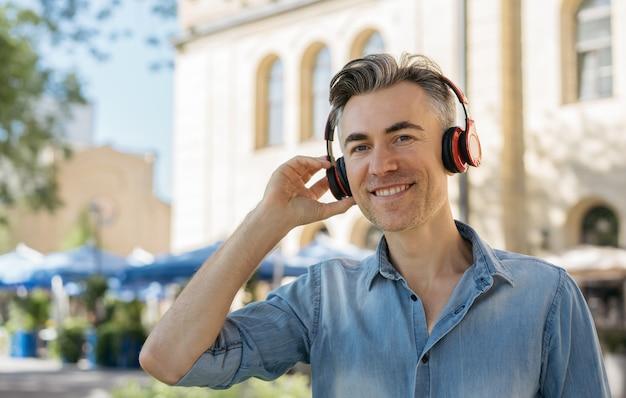 Portrait d'homme mûr souriant, écouter de la musique