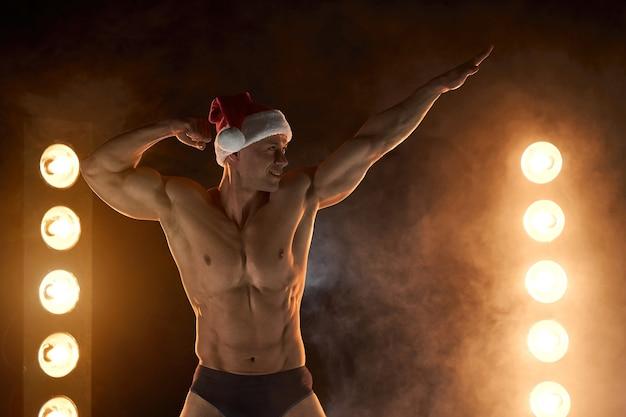 Portrait d'un homme musclé portant un bonnet de noel de noël, pose athlétique debout sur fond enfumé