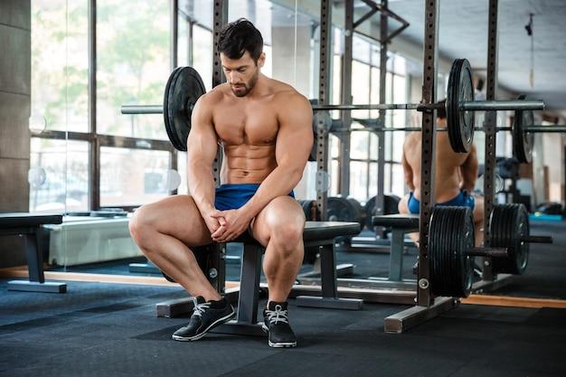 Portrait d'un homme musclé se reposant sur le banc dans la salle de fitness