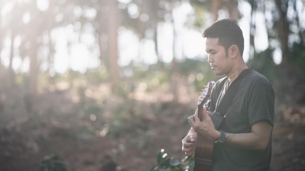 Portrait homme musicien avec guitare à la forêt