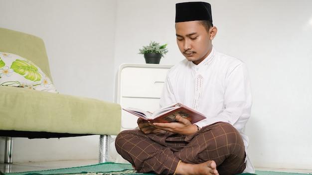Portrait d'un homme musulman asiatique lisant le saint coran à la maison