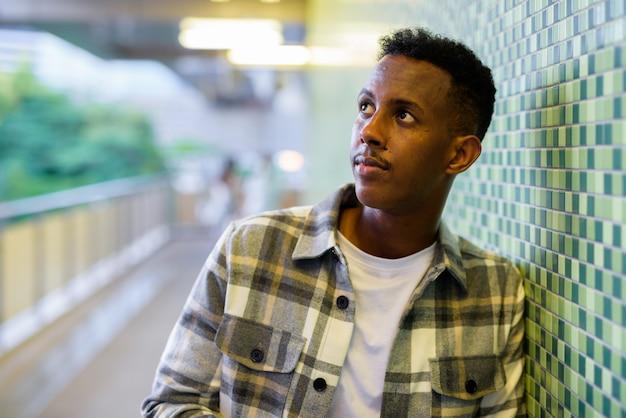 Portrait d'un homme noir africain à l'extérieur de la ville pendant l'été appuyé contre le mur la nuit tout en pensant à une prise de vue horizontale