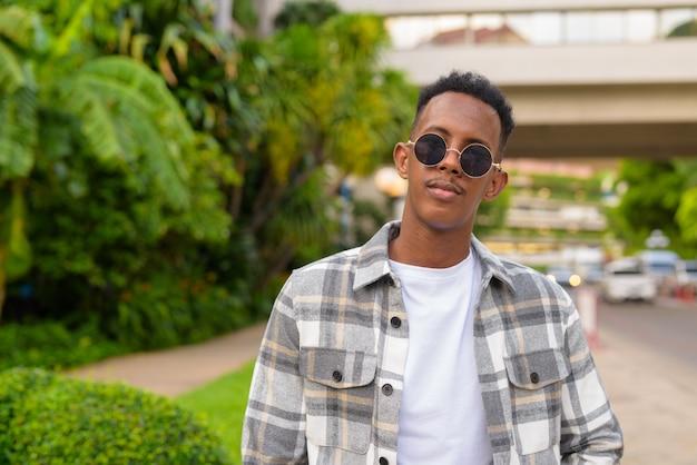 Portrait d'un homme noir africain à l'extérieur en ville pendant l'été portant des lunettes de soleil