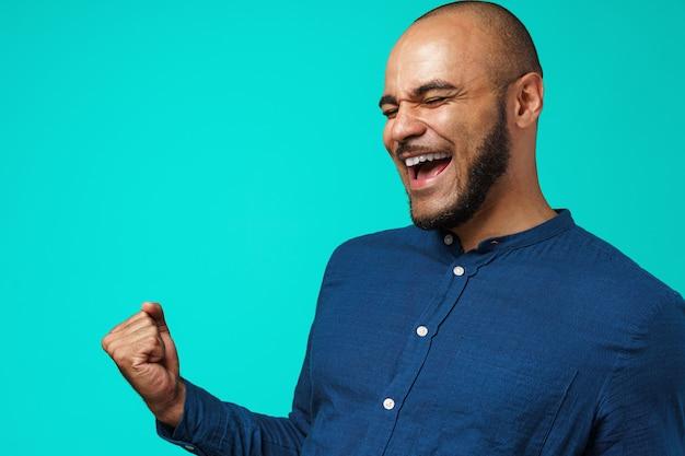 Portrait d'un homme noir heureux célébrant son succès exprimant la joie